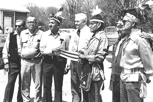 In early 1976 Chiefs of the Six Nations met with Dr. Theodore Mars, special aide to President Gerald Ford at Onondaga Longhouse. (Mars is the gray haired man in the white shirt.) The leaders explained the history to Dr. Mars using the Wampum Belts. The meeting resulted in a July 16, 1976 meeting between the Chiefs and President Ford. People: (Left to Right) Floyd Henhawk, Gordon Peters, Roy Buck, Dr. Mars, Corbett Sundown, Two Ax, Tadodaho Leon Shenandoah