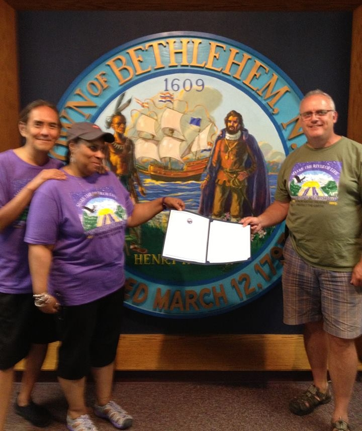 Paul Miller and Mickey Willard hold the resolution just passed in support of the Two Row Wampum Renewal Campaign by the Town of Bethlehem, July 24, 2013. Dennis Willard joins them.